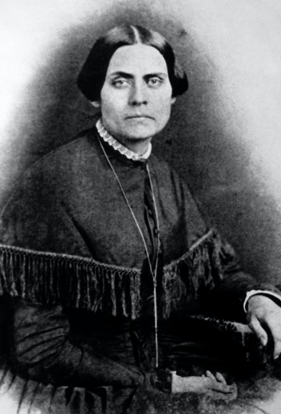 Susan B. Anthony sits in a dark dress and white collar in this black-and-white illustration.