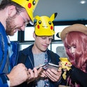 A trio of Pokemon players are seen hovering over their phones.