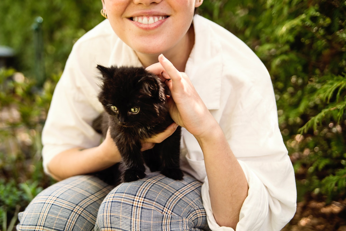 A woman holds a little black kitten, while sitting outside.
