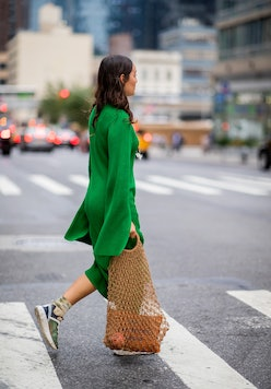 Rachael Wang in a sweater dress and sneakers.