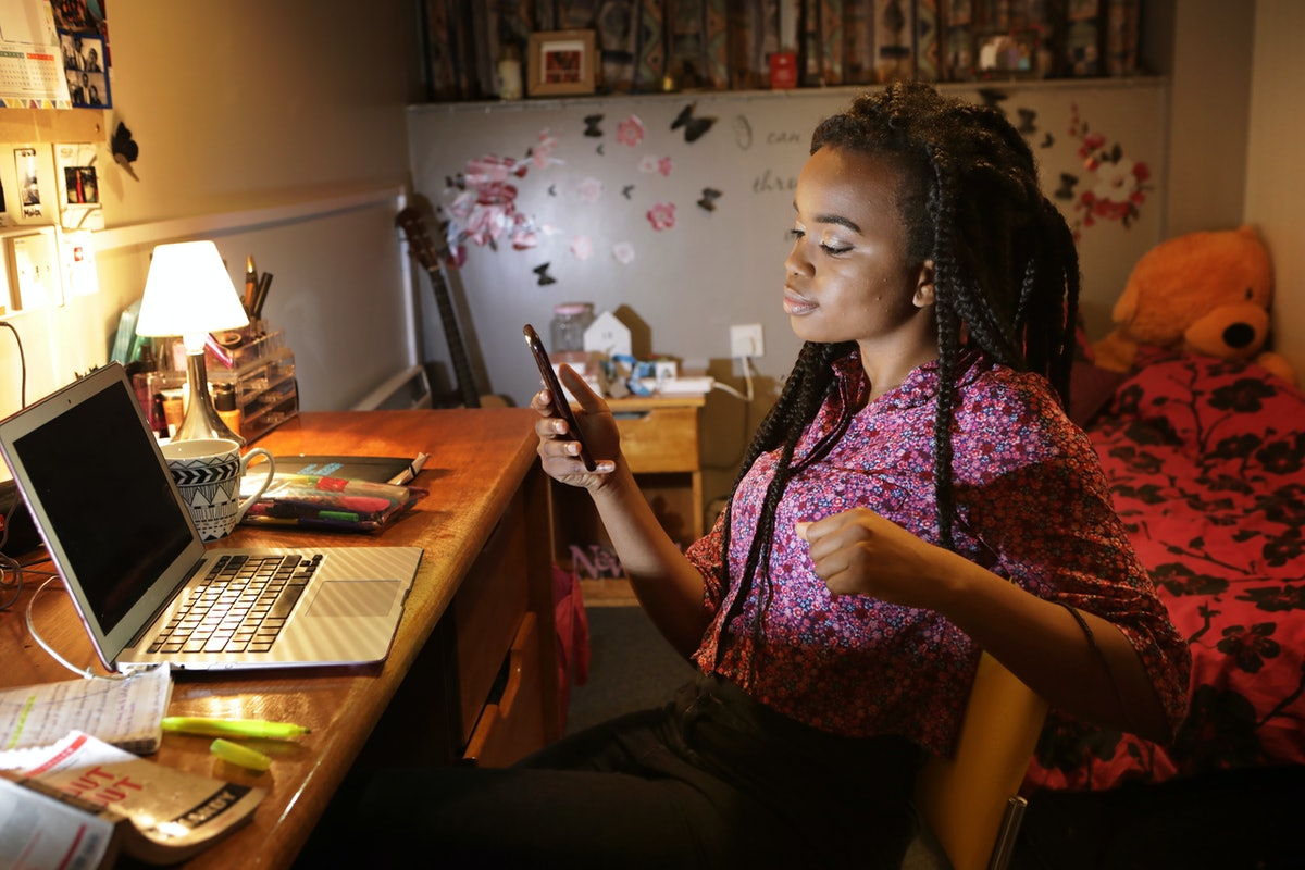 A young woman looks at her phone while sitting at her desk and completing homework at night.