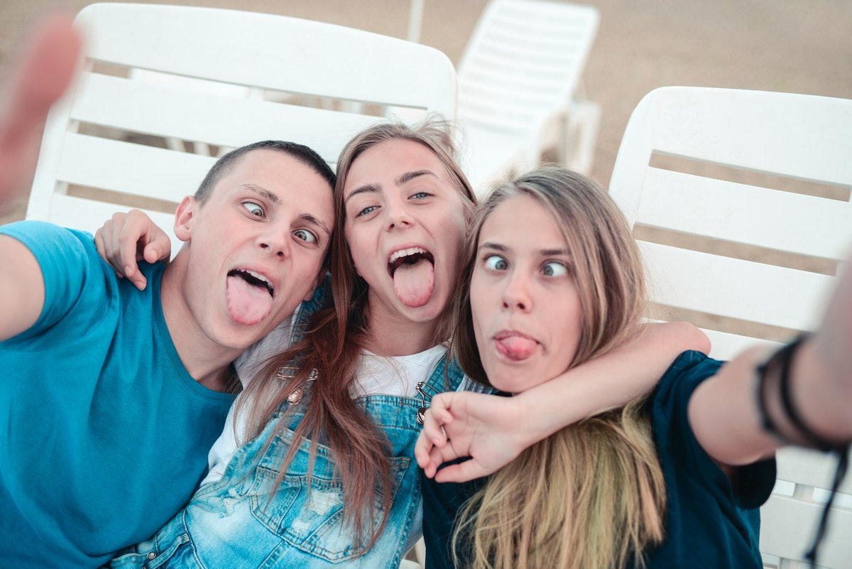 Three siblings make funny faces while posing for a selfie on their phone.