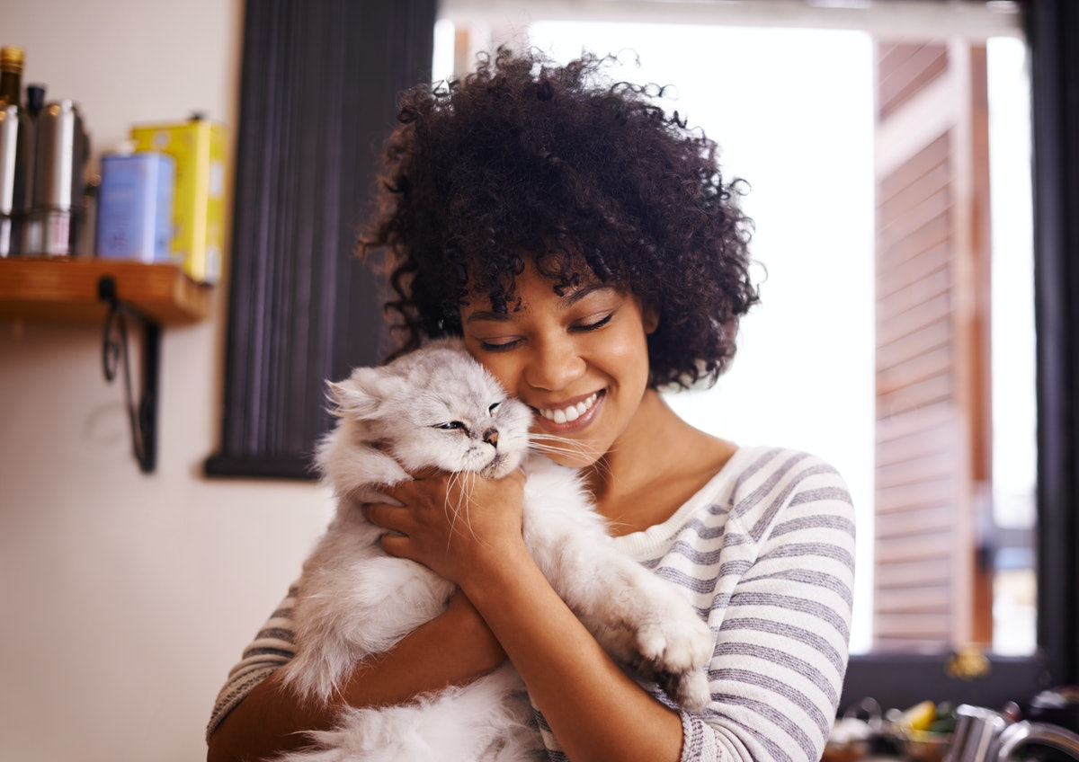 A happy woman hugs her fluffy white cat at home.