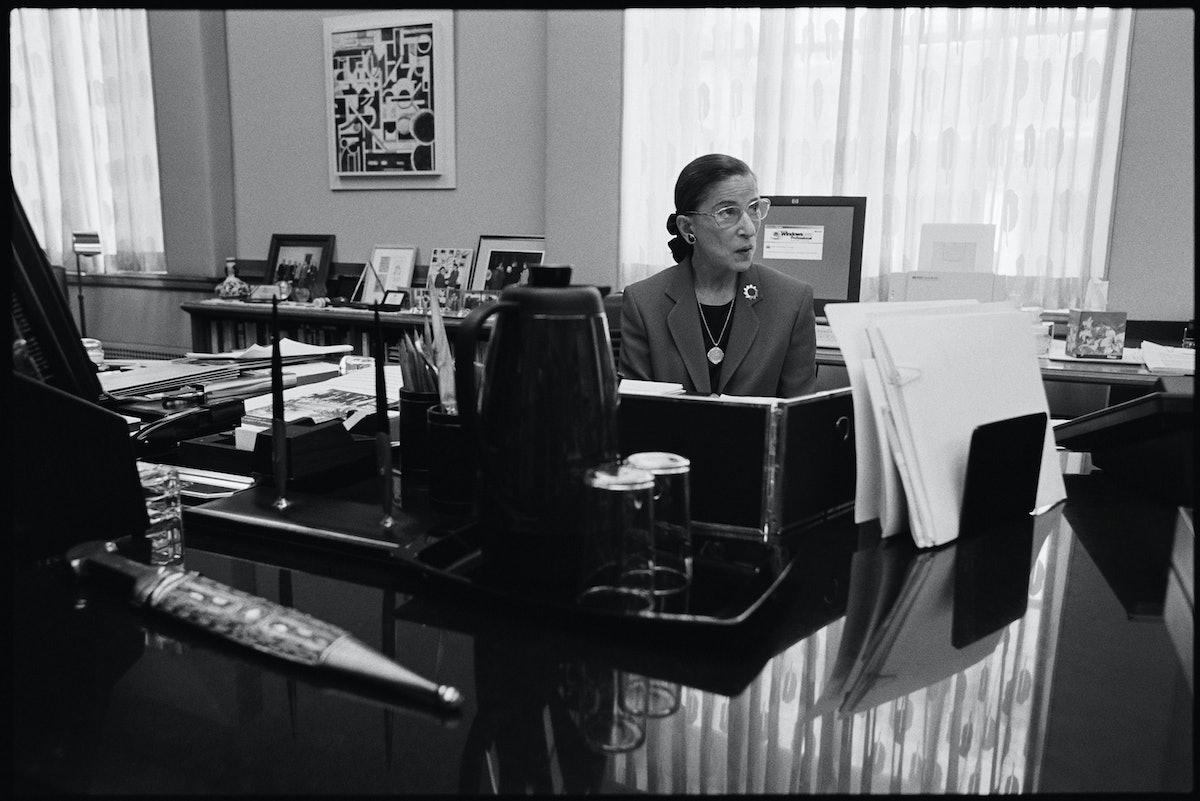 Ruth Bader Ginsburg sits at her desk.