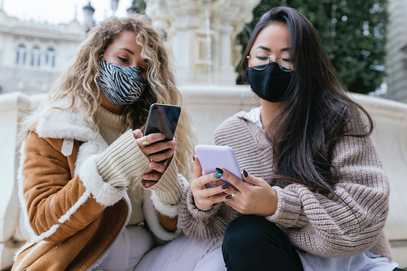 Two people wearing masks and looking at their phones wondering how the new COVID-19 variants are different from the original strain.
