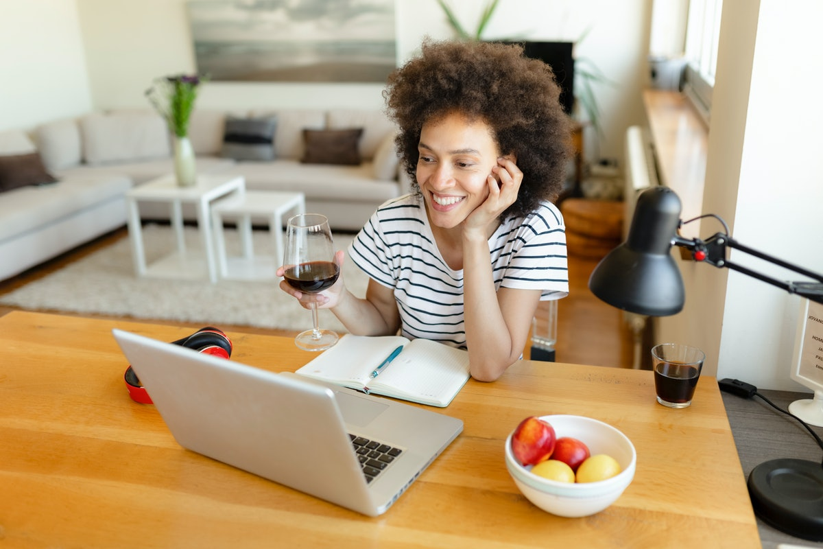 A happy woman holds a wine glass while taking a virtual class during Women's History Month.