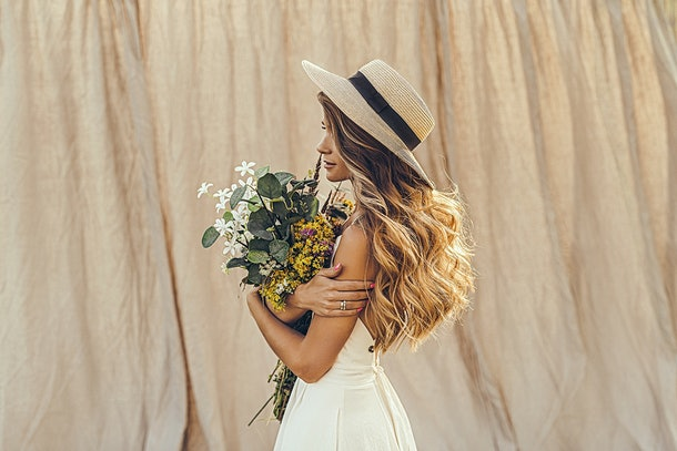 A young woman stands in front of a neutral backdrop, while wearing a hat and holding a bouquet of flowers.