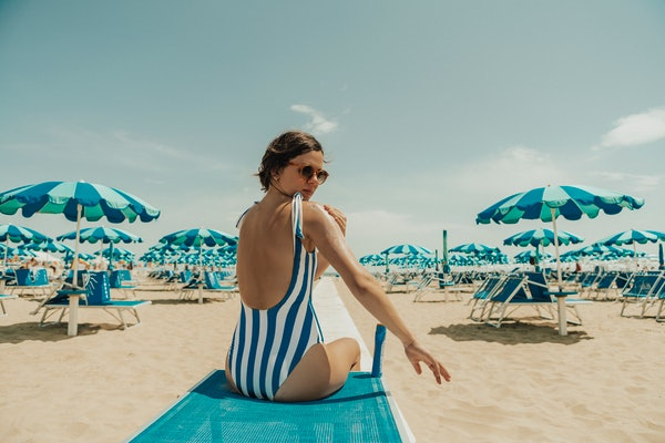 A young woman sits on a blue lounge chair on the beach, and poses for a throwback bathing suit pic for Instagram.