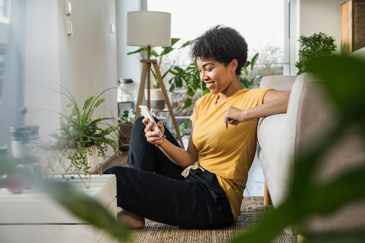 A woman looks at her phone in her living room. Twitter's Super Follows feature was announced on an investor call.