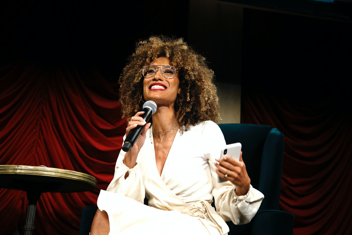 Elaine Welteroth, the youngest editor-in-chief of 'Teen Vogue,' speaks at an event while wearing a white dress and holding her phone.