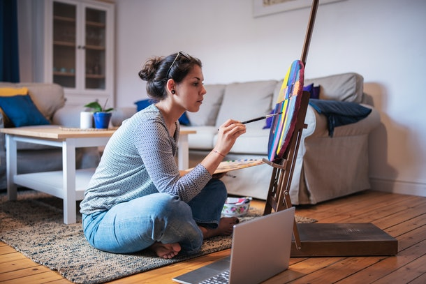 A woman sits on the floor and paints a portrait while taking a virtual paint class in her home.