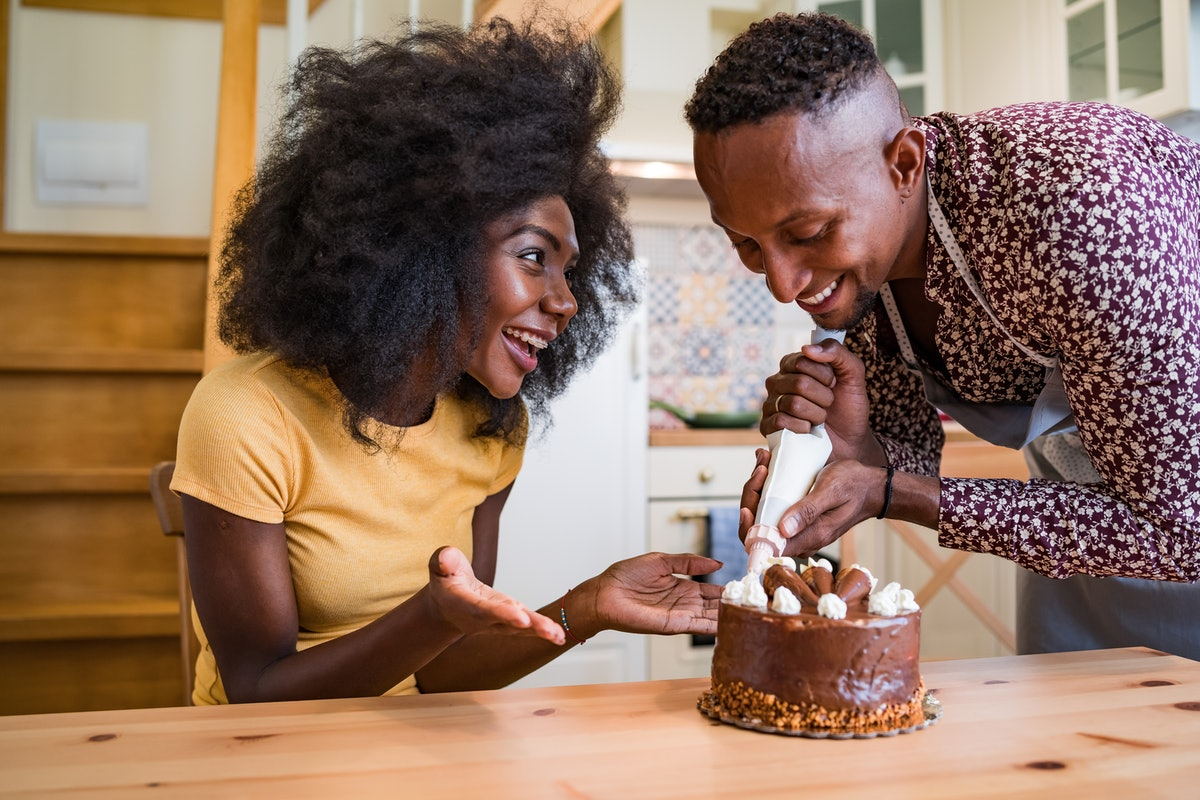 A happy couple decorates a mini cake for Super Bowl Sunday.