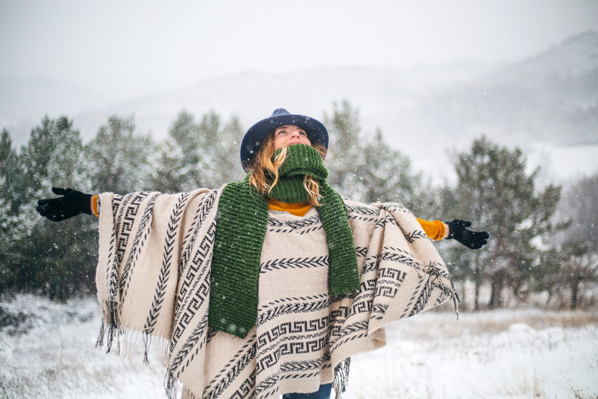A happy woman wearing a wrap, scarf, and hat looks up while enjoying a fresh snowfall.