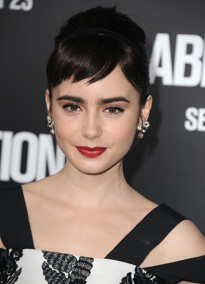 Lily Collins attends the 2011 premiere of Abduction, wearing red lipstick with an updo