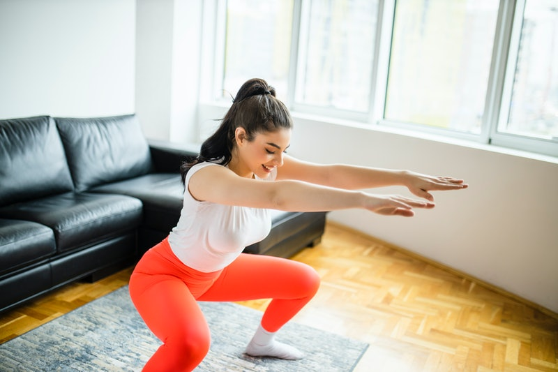 woman doing a squat, a move that's typical for a HIIT workout for beginners