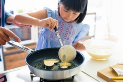 young girl making pancakes for mother's day