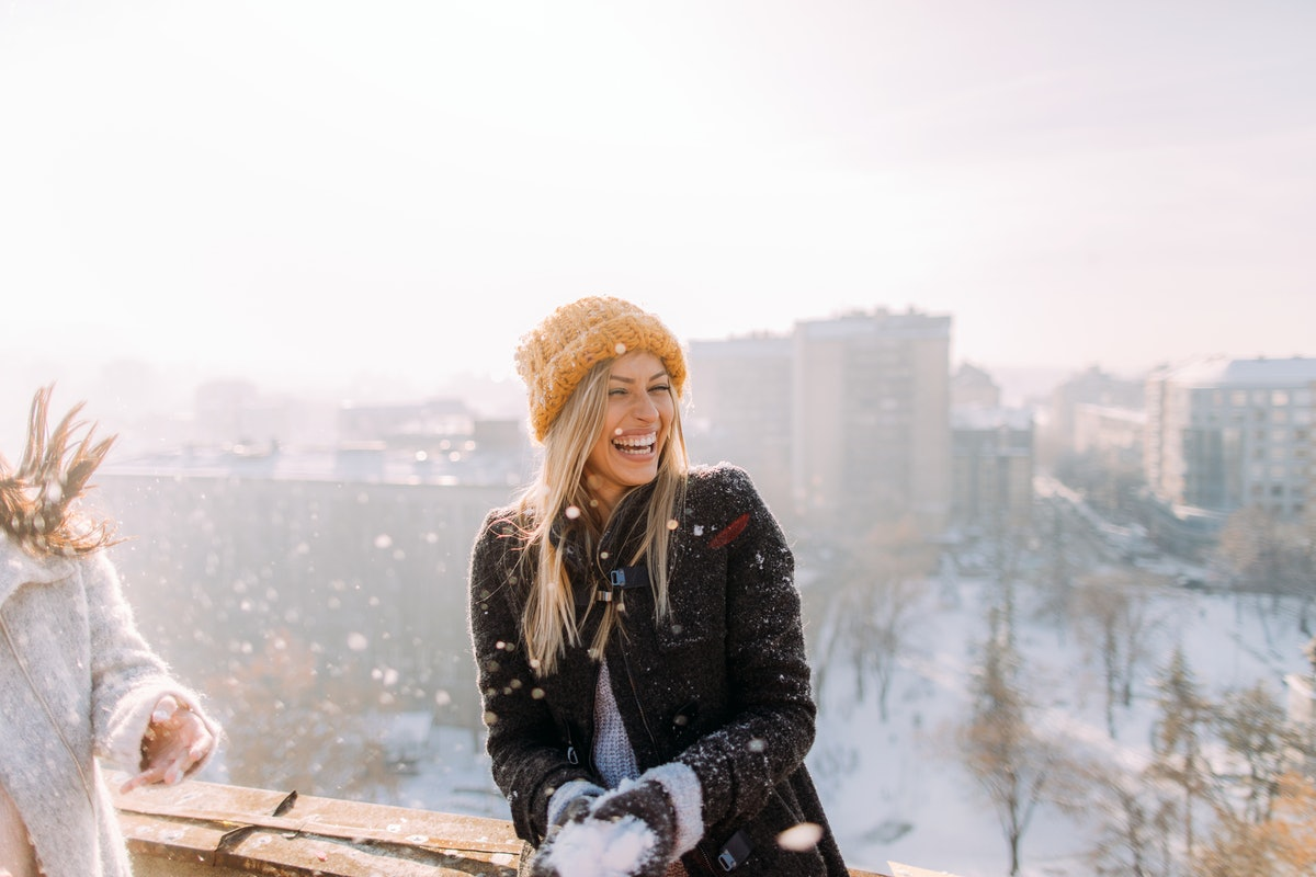 A blonde woman wearing a yellow beanie and black jacket laughs while preparing a snowball on a sunny winter day.