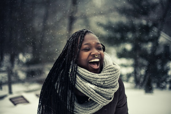 A happy woman wearing a scarf and puffer jacket laughs in the snow on a winter day.