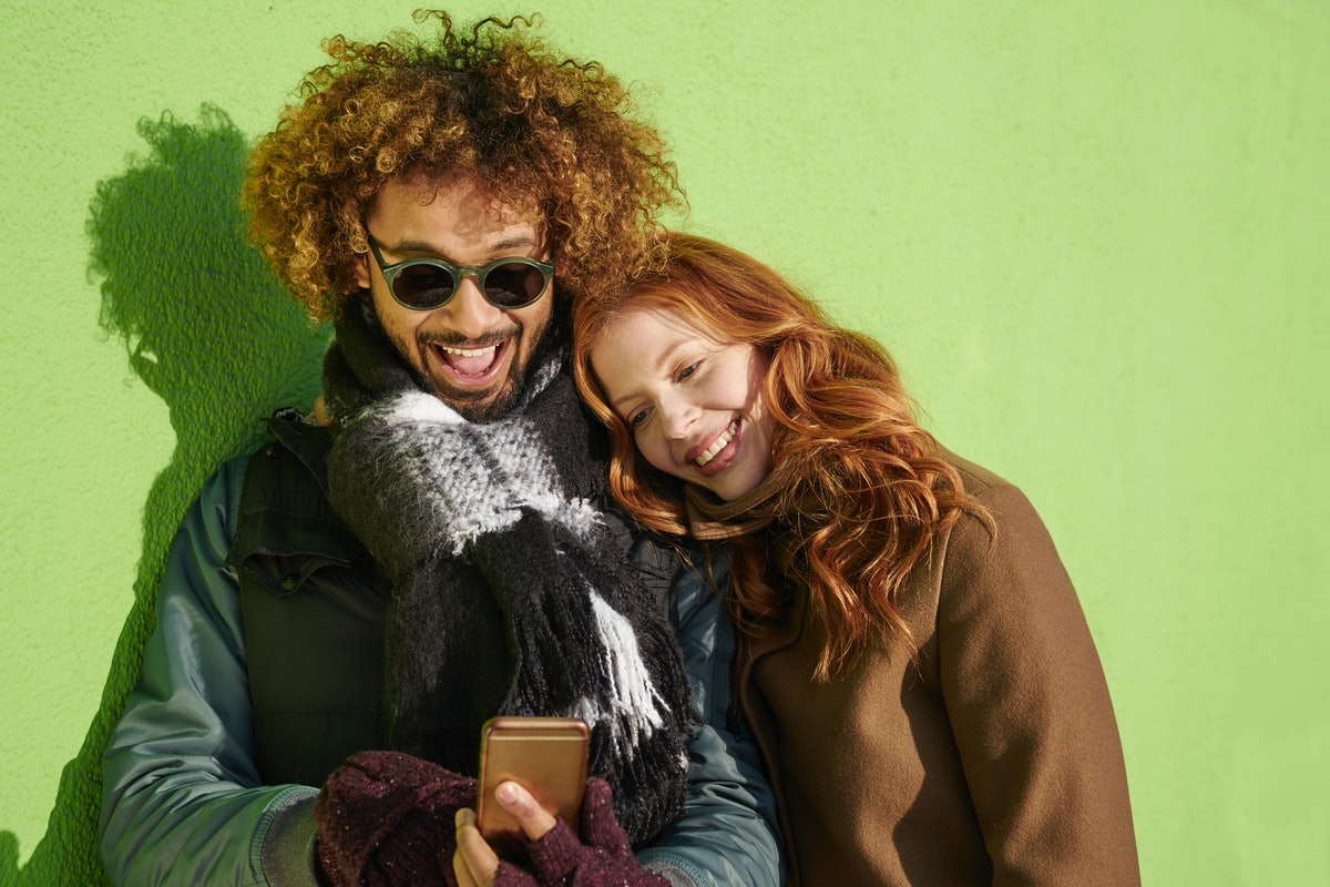 A happy couple dressed for winter leans against a lime green wall and smiles while texting in a couples group chat.