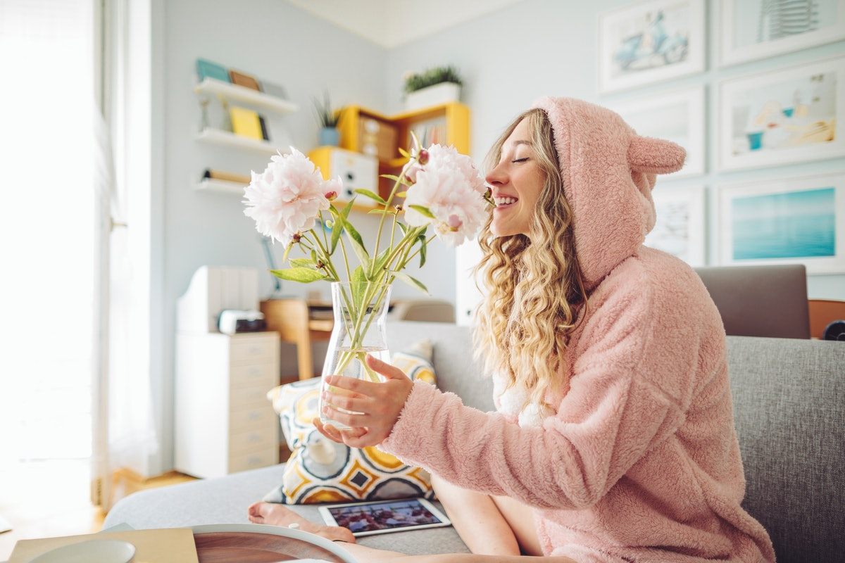 A woman in pink loungewear smells some flowers at home on Valentine's Day.
