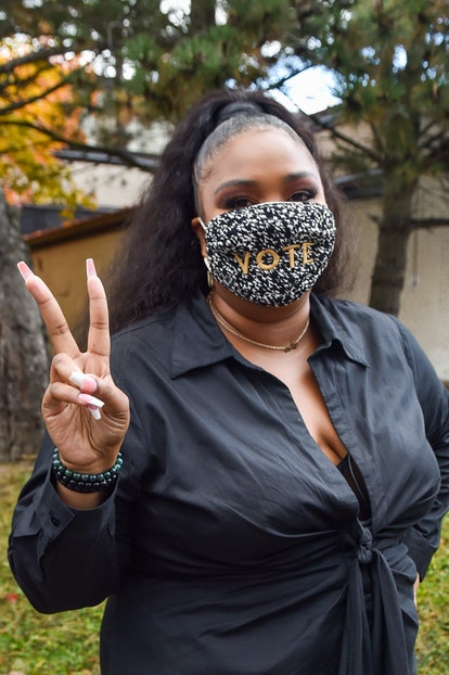 """Lizzo wears a """"Vote"""" mask and flashes a peace sign."""