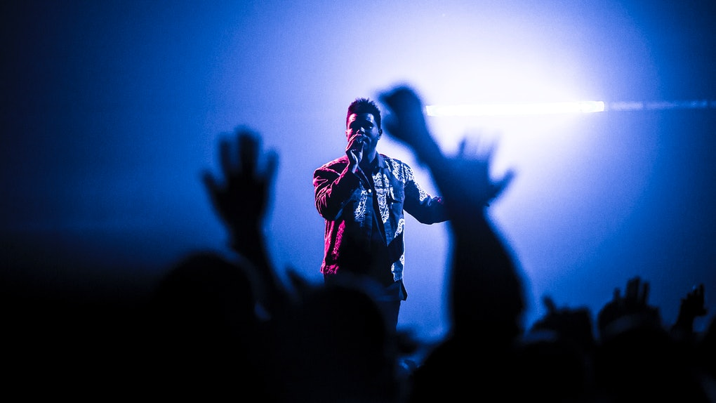 The Weeknd performs to a small crowd of people while his stage is lit up blue and pink.