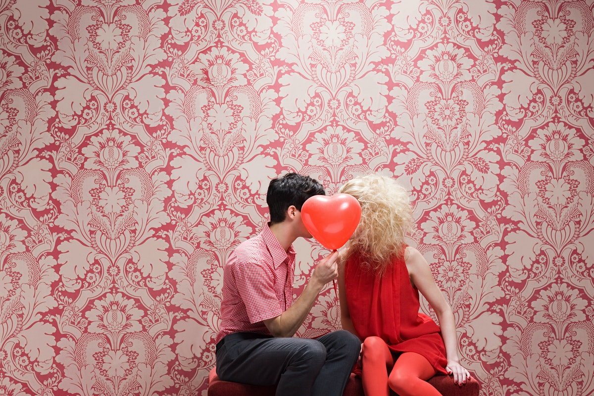 A young couple kisses behind a heart-shaped balloon in a throwback Valentine's Day picture.