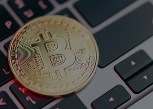 Physical gold bitcoin resting on a laptop keyboard.