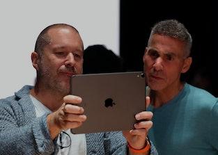 Apple executives Jony Ive and Dan Riccio look into the screen of an iPad.