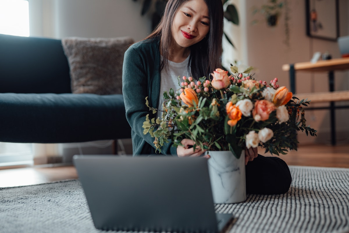 A smiling woman sits in front of her laptop with a beautiful bouquet of flowers while on a virtual V...
