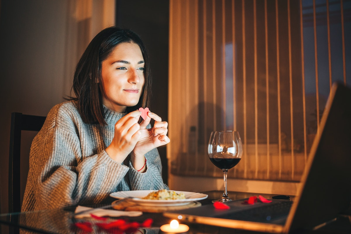 A cozy woman holds a paper heart to her laptop in front of wine and dinner while on a virtual Valent...