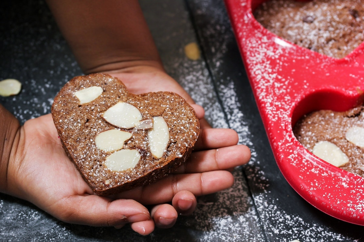 A woman holds a heart-shaped brownie.