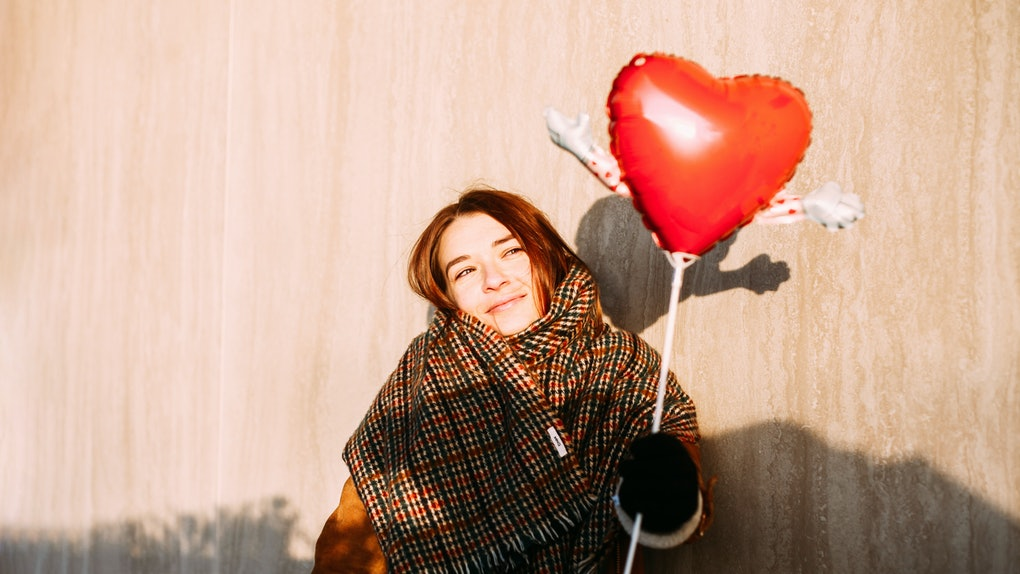 A young woman poses in the sunshine with a heart-shaped balloon for a Valentine's Day photo session.