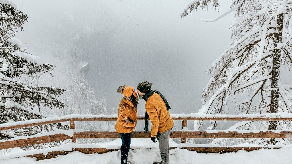 A couple kisses by a scenic overlook while on a snowy winter hike.