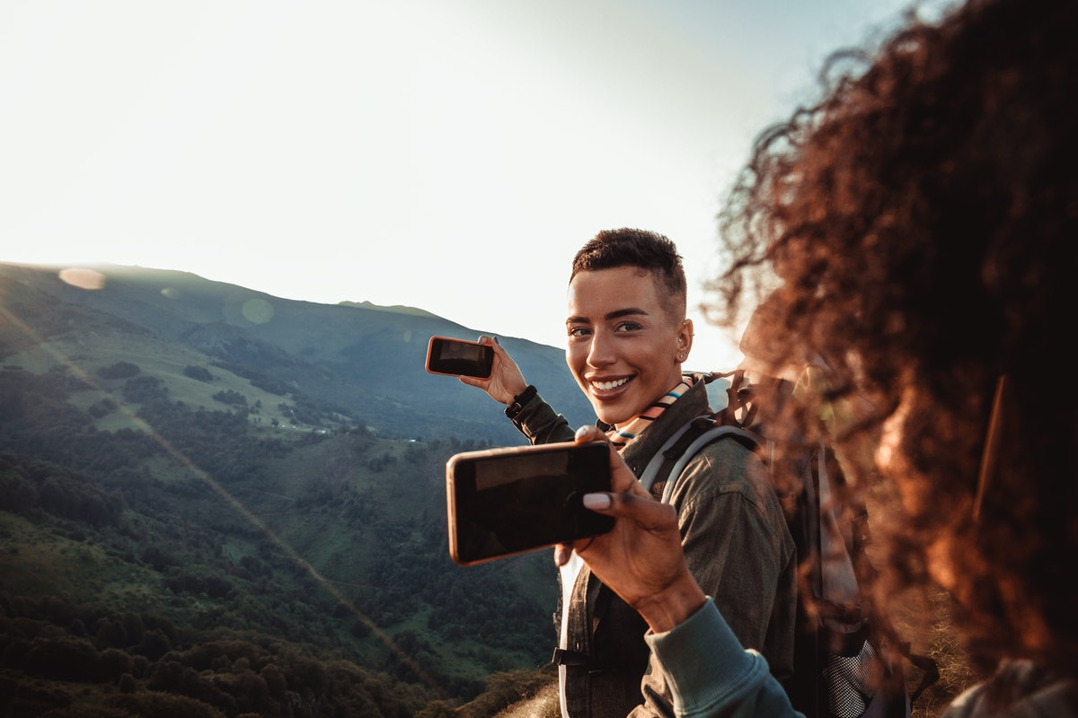 A woman smiles while taking a picture at the top of a hike with her partner.