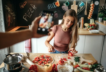 A woman cuts veggies for a pizza wrap while her partner takes a picture for TikTok.