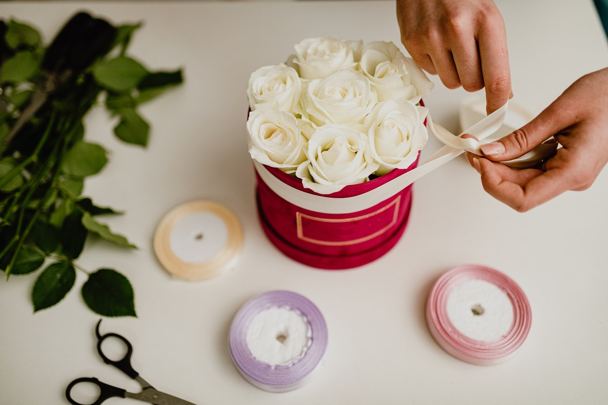 A young woman ties a ribbon around a bouquet of flowers after watching a Valentine's Day DIY TikTok ...