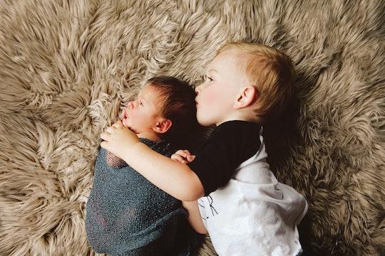 toddler holding baby sibling