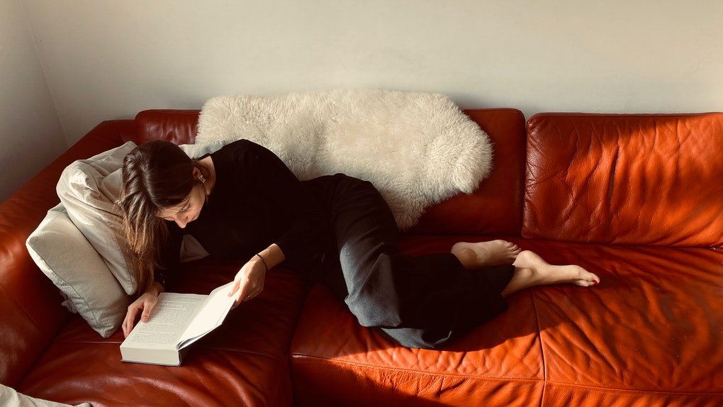 A single woman relaxes on a red leather couch and reads a romance book on Valentine's Day.