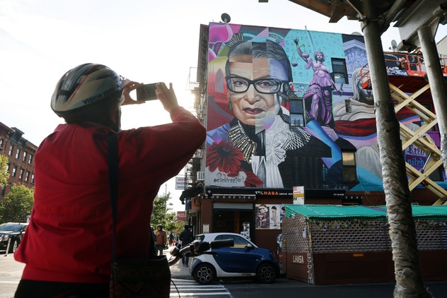 woman taking a picture of ruth bader ginsburg mural