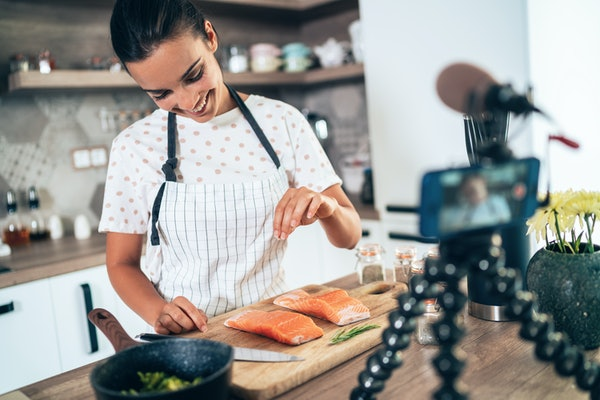 A woman cooks salmon in her kitchen.