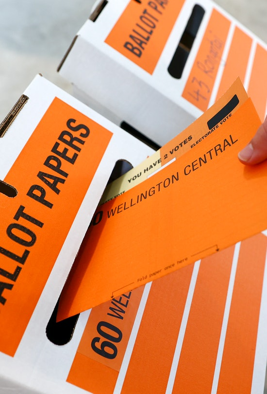 """An orange ballot envelope is slipped into a white-and-orange collection box marked """"ballot papers."""""""