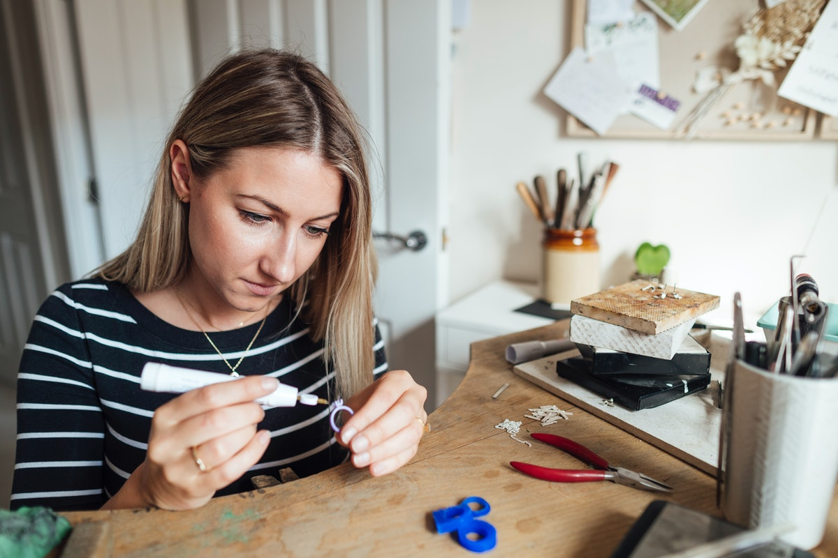 A woman crafts a ring uses glue and pliers for a fun DIY at home.