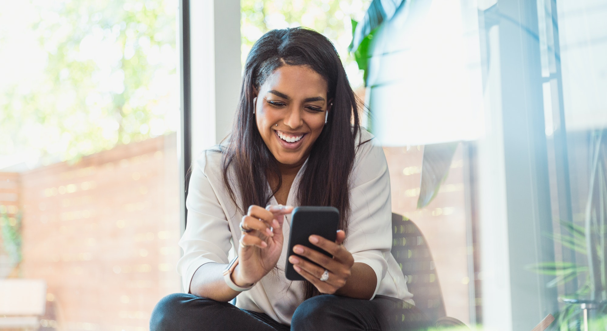 A woman looks at her phone laughing at Twitter's Super Follows feature.