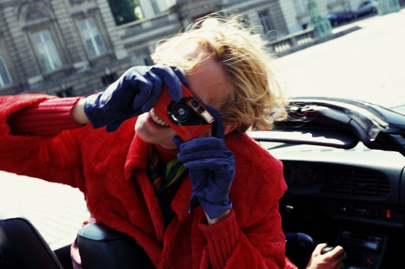 A person uses a disposable camera. These apps like dispo mimic the disposable camera experience.