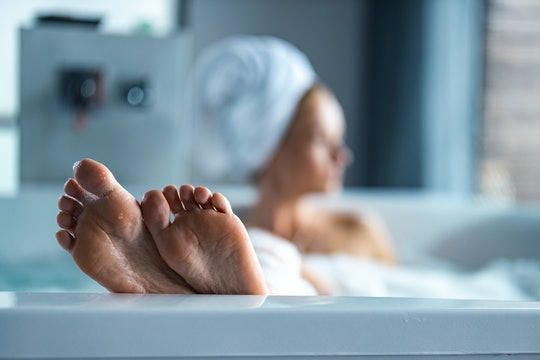Close up of unrecognizable woman relaxing during her bubble bath in a bathroom.