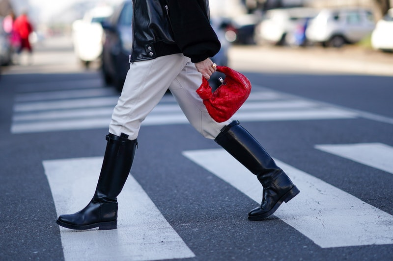 MILAN, ITALY - FEBRUARY 22: A guest wears rings, a black leather jacket with black suede sleeves , white leather pants, black riding boots, a red woven leather handbag, outside MSGM, during Milan Fashion Week Fall/Winter 2020-2021 on February 22, 2020 in Milan, Italy. (Photo by Edward Berthelot/Getty Images)