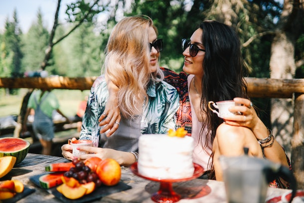 Vintage toned image of two young women enjoying their time together in the beautiful nature, having lunch, drinking wine, wearing fashionable boho clothes.
