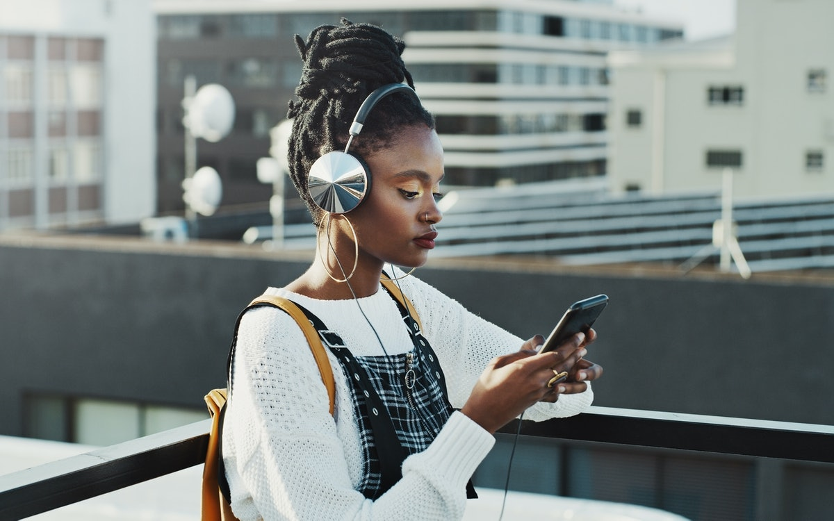 Shot of an attractive young woman using a smartphone to listen to music in the city
