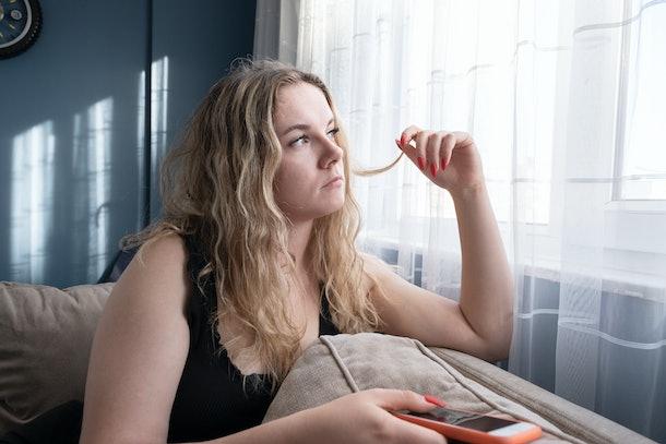 Sad young woman using mobile phone on sofa. Horizontal composition.